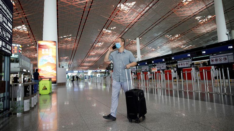 A man wearing a face mask uses a mobile phone at the departure hall of Beijing Capital International Airport after scores of domestic flights in and out of the Chinese capital were cancelled following the new outbreak of the coronavirus disease (COVID-19) in Beijing, China June 17, 2020. REUTERS/Carlos Garcia Rawlins