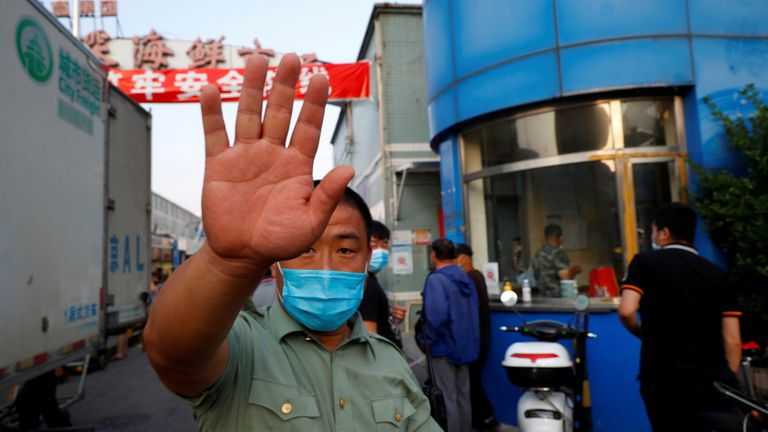 A security guard wearing a face mask tries to block the camera outside the Jingshen seafood market which has been closed for business