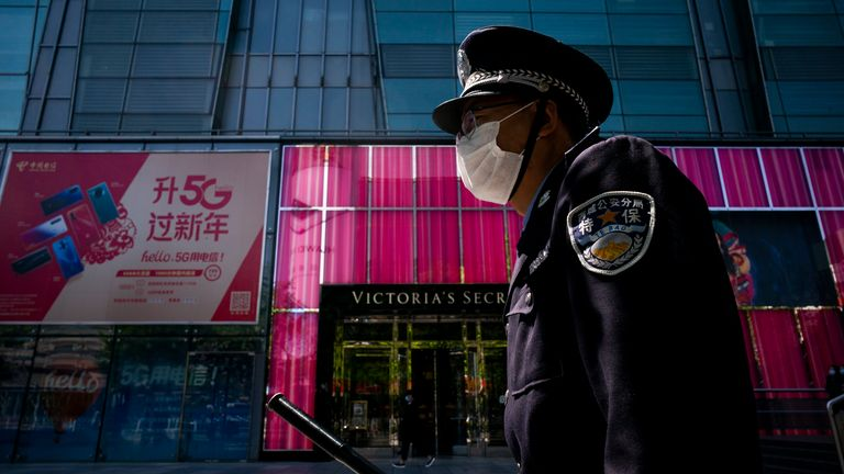 A security guard wears a protective mask as he walks in the street on April 23, 2020 in Beijing, China