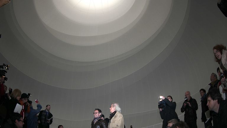 Bulgarian-born artist Christo (R), known for his large-scale environmental art, and his photographer Wolfgang Volz lead journalists through his Big Air Package, his latest work in a former gas storage facility called the Gasometer on March 15, 2013 in Oberhausen, Germany. The piece is made from 5.3 tons of translucent material covering 20,350 square meters and shaped with 4.500 meters of cable, and fills the interior of the facility. The installation will be open