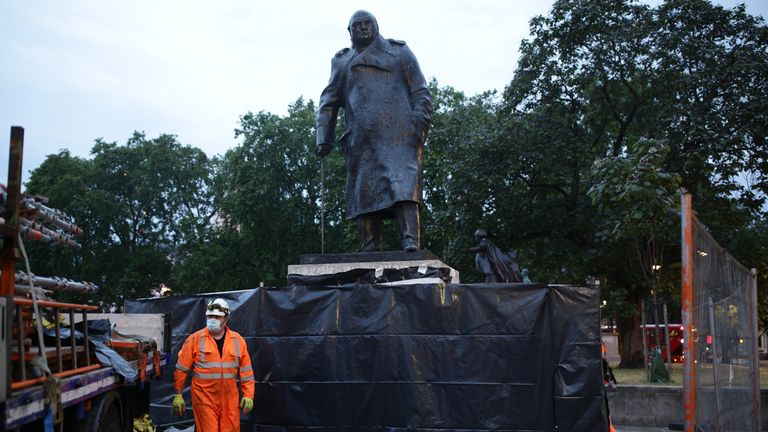 Workers finish taking down boarding and scaffolding around the Winston Churchill statue