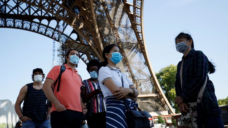 Visitors wearing protective facemasks queue as they wait for the partial reopening of Eiffel Tower on June 25, 2020, in Paris, as France eases lockdown measures taken to curb the spread of the COVID-19 caused by the novel coronavirus. - Tourists and Parisians will again be able to admire the view of the French capital from the Eiffel Tower after a three-month closure due to the coronavirus -- but only if they take the stairs. (Photo by Thomas SAMSON / AFP) (Photo by THOMAS SAMSON/AFP via Getty I