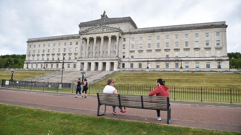 Friends observe social distancing as they meet outside Stormont in Belfast, Northern Ireland
