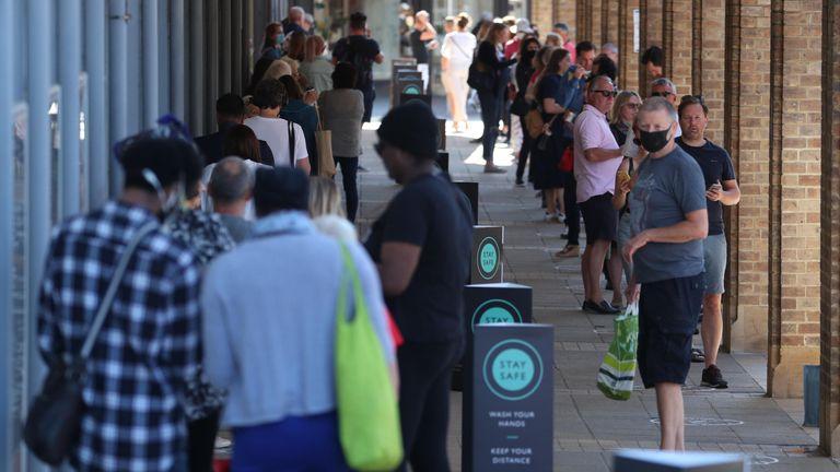 Shoppers queue outside a John Lewis store in Kingston, London