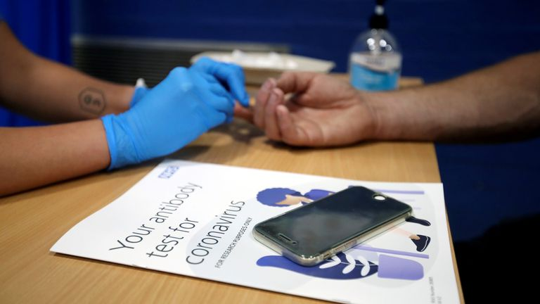A man has his finger pricked during a clinical trial of tests for the coronavirus disease (COVID-19) antibodies, at Keele University, in Keele, Britain June 30, 2020. REUTERS/Carl Recine