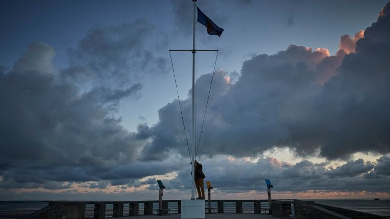Adrian Cox, a British Expat and Councilor of Arromaches, raises the flag of the Normandy Veterans Association at dawn to commemorate the 76th Anniversary of the D-Day landings at dawn on Gold Beach on June 06, 2020 in Arromanches-les-Bains, France. Due to Covid-19 travel restrictions this is the first time in 75 years that veterans have not been able to attend the Anniversary. (Photo by Kiran Ridley/Getty Images)