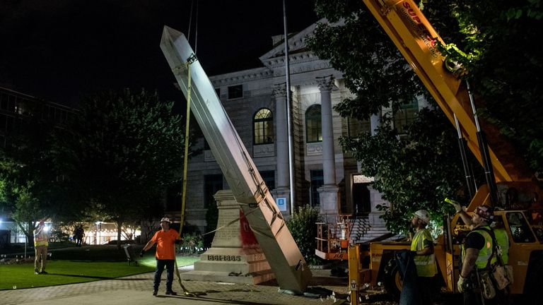 Crew members work to remove the the 30-foot Confederate monument which is been brought down on June 19, 2020, in Decatur northeast of Atlanta, Georgia