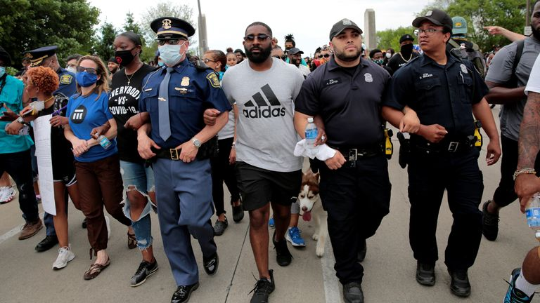 Protesters walked arm-in-arm with police in Detroit, Michigan