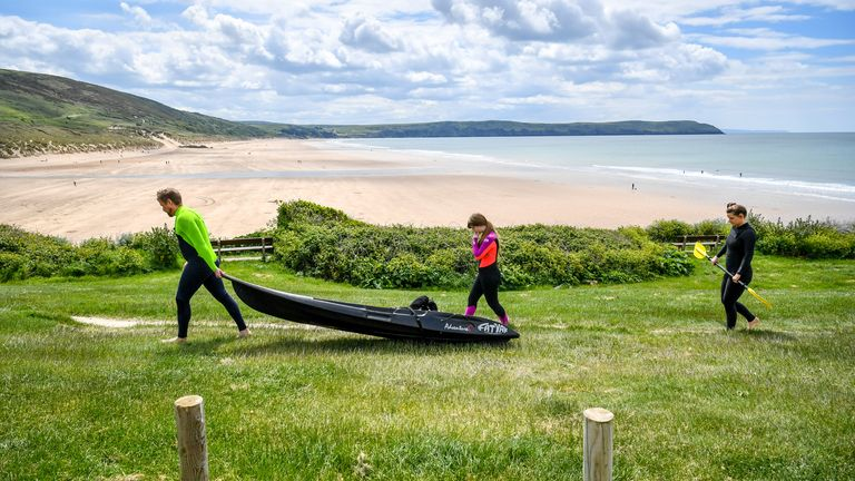 Kyakers wear wetsuits as they make their way towards the beach in Woolacombe, Devon.
