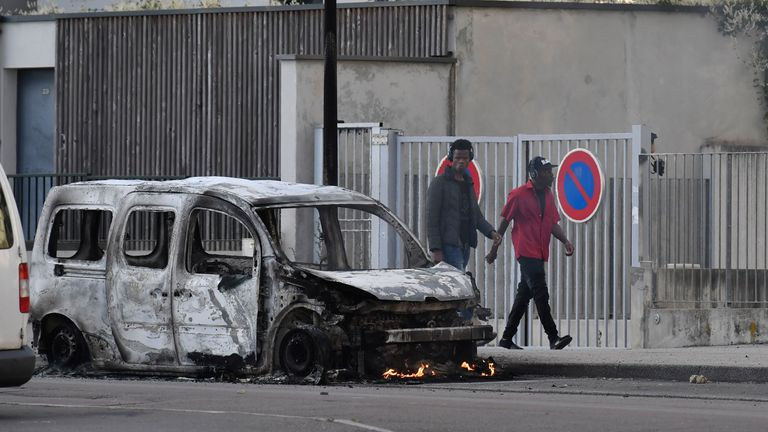 People walk past a burnt van in the Gresilles area of Dijon, eastern France, on June 15, 2020, as new tensions flared in the city after it was rocked by a weekend of unrest blamed on Chechens seeking vengeance for an assault on a teenager. - Police sources said the unrest was sparked by an attack on a 16-year-old member of the Chechen community on June 10. Members of the Chechen diaspora then set out on so-called punishment raids seeking to avenge the assault, they said. After three successive n