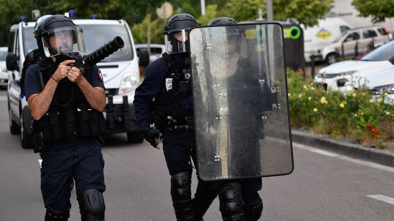 Police walk carrying a shield and a tear gas canister launcher in the Gresilles area of Dijon, eastern France, on June 15, 2020, as new tensions flared in the city after it was rocked by a weekend of unrest blamed on Chechens seeking vengeance for an assault on a teenager. - Police sources said the unrest was sparked by an attack on a 16-year-old member of the Chechen community on June 10. Members of the Chechen diaspora then set out on so-called punishment raids seeking to avenge the assault, t