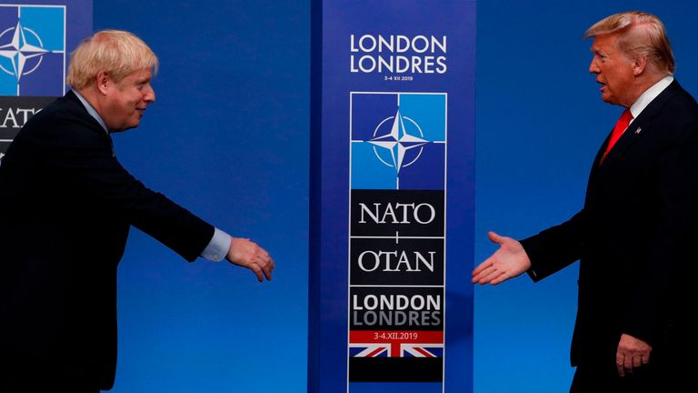 Britain's Prime Minister Boris Johnson (L) greets US President Donald Trump upon arrival for the NATO summit at the Grove hotel in Watford, northeast of London on December 4, 2019