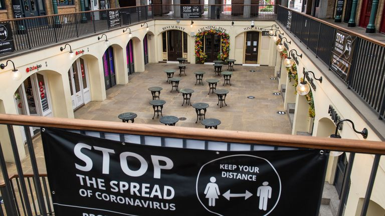 Empty tables alongside a social distancing sign in Covent Garden market, London, as further coronavirus lockdown restrictions are lifted in England.