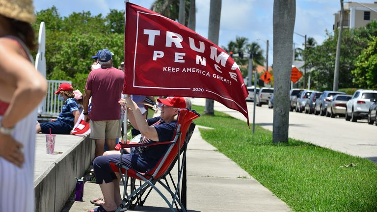 Supporters of President Donald Trump wave their flags as a Flotilla of Boaters sail by on inter-coastal waterways at Mar-a-Lago