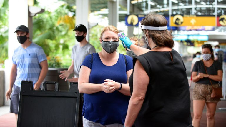 A Universal Studios employee takes the temperature of a guest during the first day of reopening from the coronavirus pandemic at Universal Orlando Resort on June 05, 2020 in Orlando, Florida. (Photo by Gerardo Mora/Getty Images,)