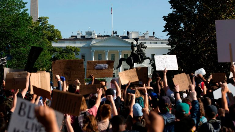 TOPSHOT - Demonstrators hold up placards protest outside of the White House, over the death of George Floyd in Washington D.C. on June 1, 2020