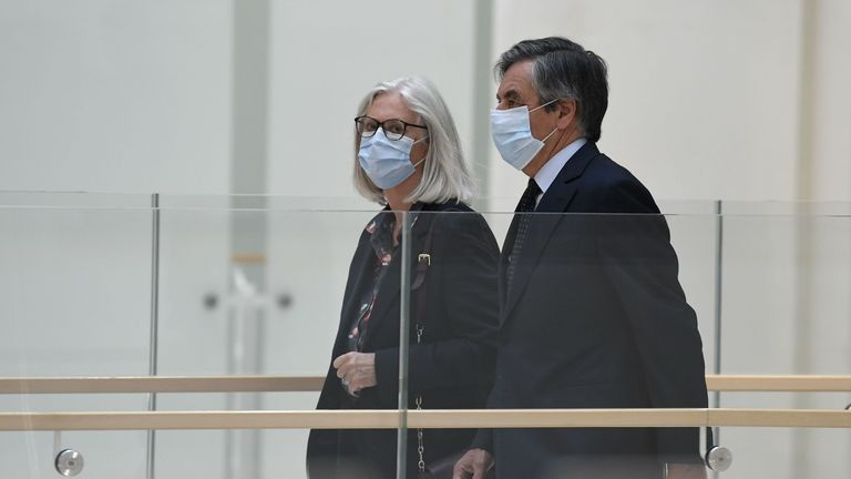 Former France PM Francois Fillon (L) and his wife Penelope Fillon (C) arrive at court