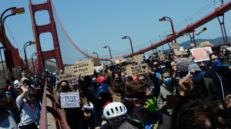 Thousands of demonstrators marched across San Franciso's Golden Gate Bridge, blocking motorists who honked their horns in support