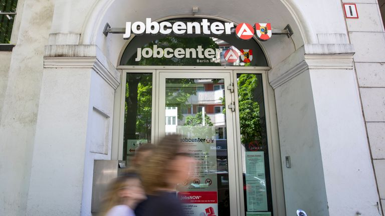 People pass by an employment agency in Berlin last month as lockdown restrictions are eased