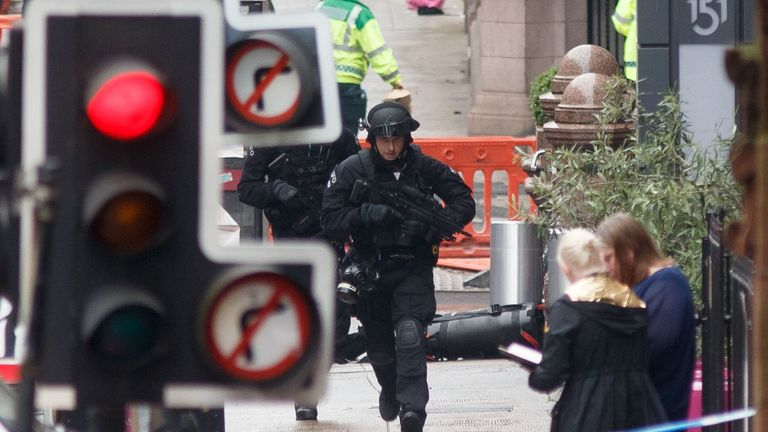 Armed specialist police officers run as they respond at the scene of a fatal stabbing incident