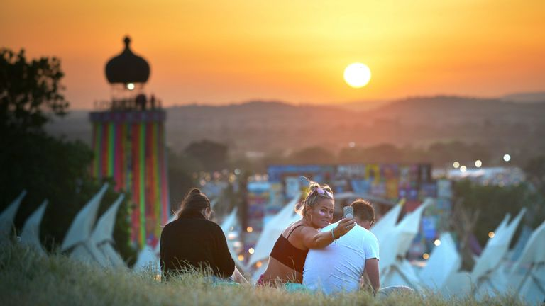 Festival goers take selfies at sunset during day two of Glastonbury Festival at Worthy Farm, Pilton on June 27, 2019 in Glastonbury, England. The festival, founded by farmer Michael Eavis in 1970, is the largest greenfield music and performing arts festival in the world. Tickets for the festival sold out in just 36 minutes as it returns following a fallow year