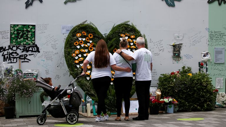 People hug during a commemoration to mark the third anniversary of the Grenfell Tower fire
