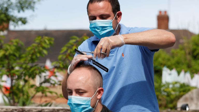 Hairdresser Pavlos cuts a mans hair in his garden as they both wear masks after his shop was shut due to government guidelines, following the outbreak of the coronavirus disease (COVID-19), Edmonton, Britain May 8, 2020