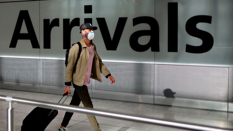 A passenger wearing a face mask as a precaution against the novel coronavirus arrive at Heathrow airport, west London, on May 22, 2020