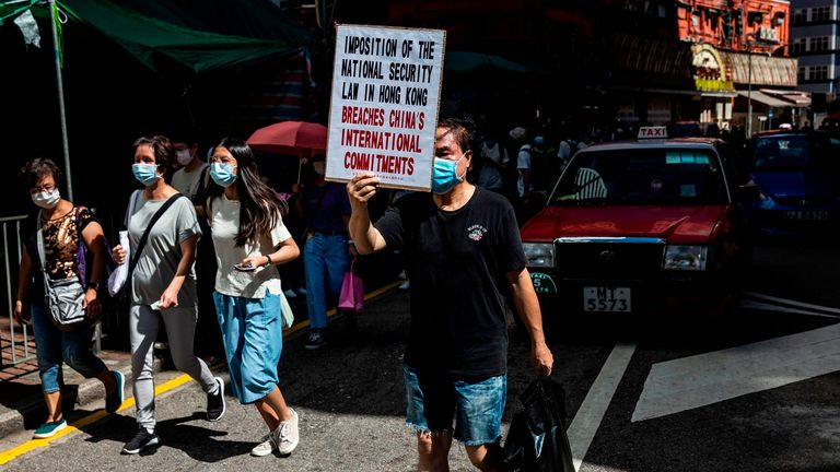 A man (C) holds a sign denouncing Chinas plans to impose a new national security law during a protest in Hong Kong on June 28, 2020. (Photo by ISAAC LAWRENCE / AFP) (Photo by ISAAC LAWRENCE/AFP via Getty Images)
