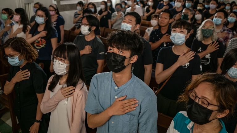 HONG KONG, CHINA - JUNE 28: Pro-democracy supporters make a gesture as they sing a song during a memorial service in a church on June 28, 2020 in Hong Kong, China. (Photo by Anthony Kwan/Getty Images)