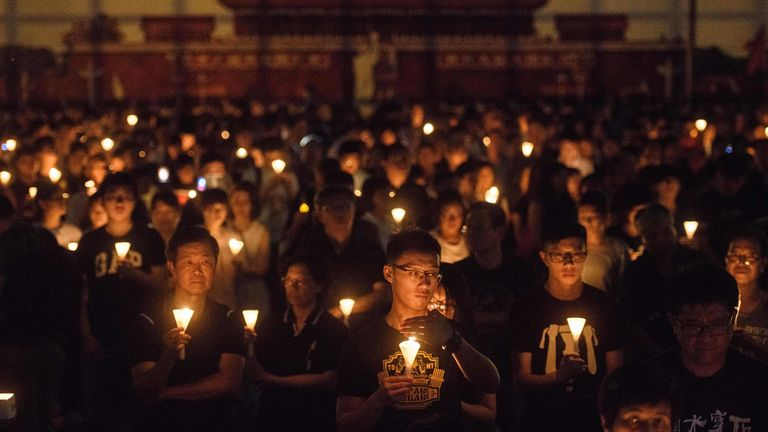 People hold candles during a Tiananmen vigil in Hong Kong in 2018