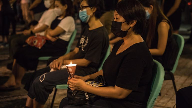 People attend a mass outside a church in Hong Kong