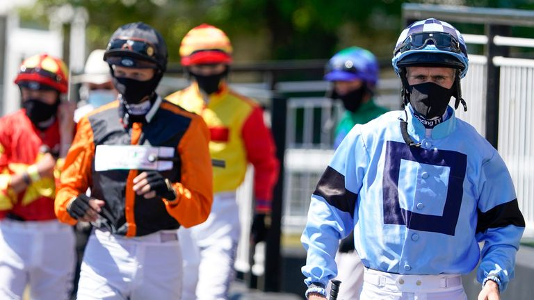 Jockeys are wearing masks at the race track in Newcastle on Monday