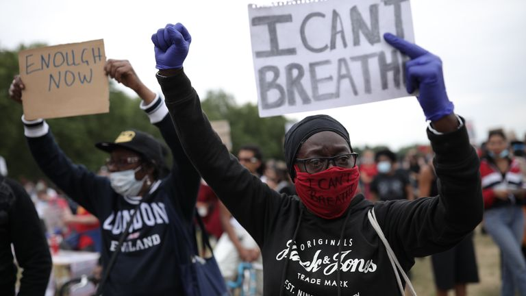 A protester wearing a face mask holds a sign saying 'I can't breathe'