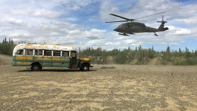 A Blackhawk hovers near the bus which was moved by a CH-47 Chinook