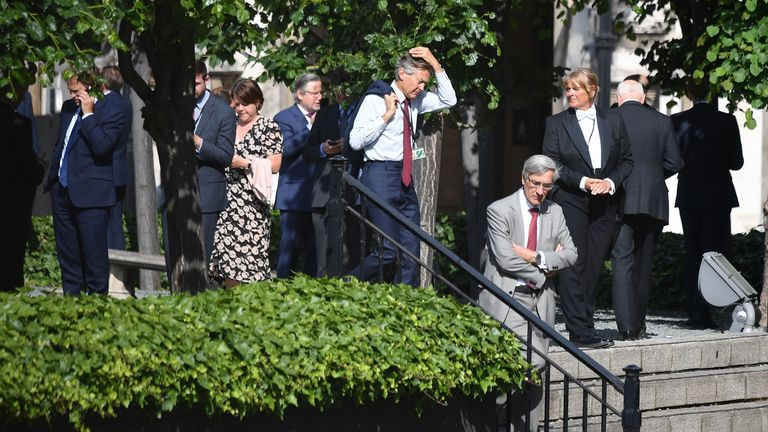 Conservative MP John Redwood (R) is seen queuing with colleagues in a courtyard on the parliamentary estate