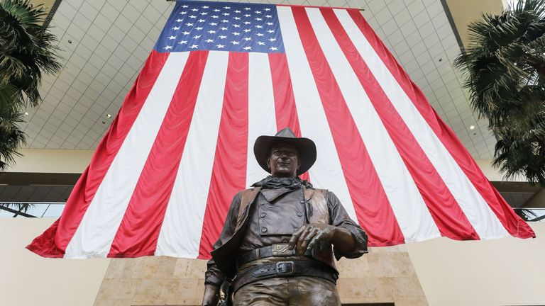 A statue of John Wayne is on display beneath an American flag in John Wayne Airport