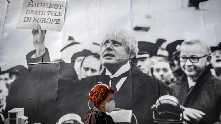 "A woman in a mask walks past a satirical poster depicting Boris Johnson as former British prime minister Neville Chamberlain delivering his ""Peace for Our Time"" speech"