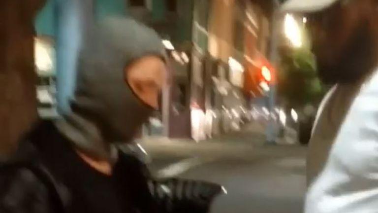 A man hands over a spray can to Jon Jones