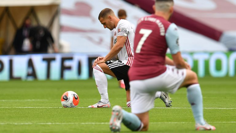 Sheffield United's Billy Sharp and Aston Villa's John McGinn take a knee as play resumes behind closed doors following the outbreak of the coronavirus disease