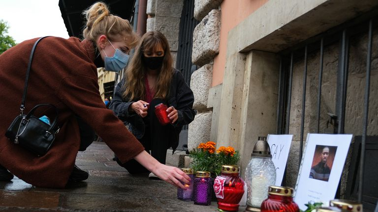 Women wear protective face masks as they light candles to place in a small memorial for George Floyd in front of the US Consulate in Krakow, Poland