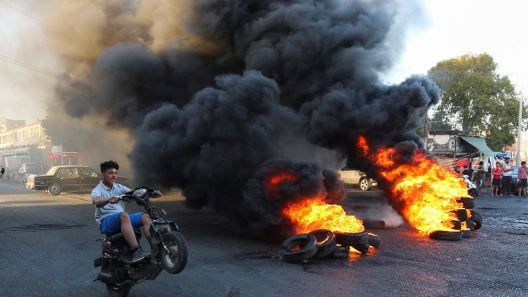 A youth rides his motorbike near burning tires during a sit-in protest against the fall in pound currency and mounting economic hardship, in Ghazieh