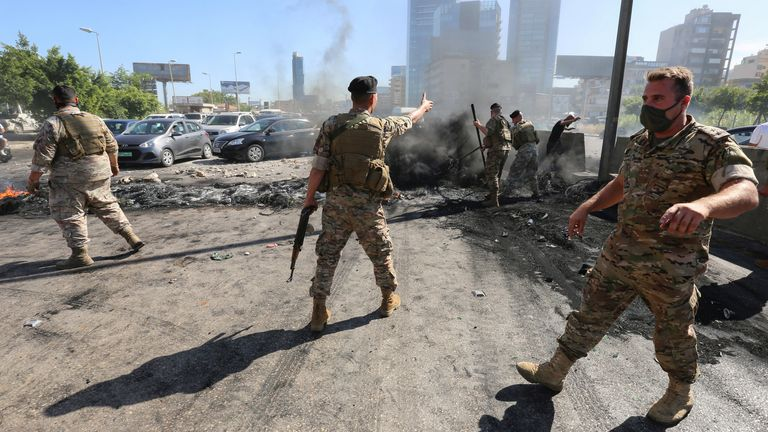 Lebanese army soldiers open a road that was blocked by demonstrators during a protest in Antelias