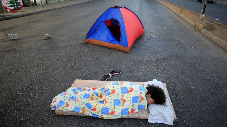 A demonstrator lies on the ground to block a road in Sidon
