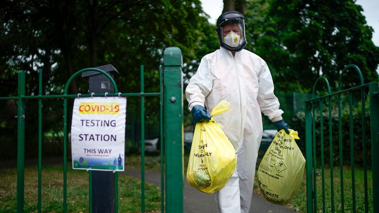 A city council worker is seen carrying rubbish from a coronavirus testing centre in Leicester