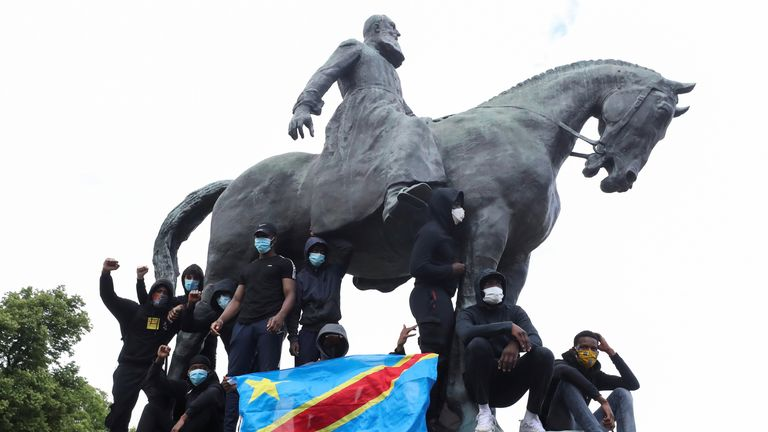 Demonstrators stand on the statue of Leopold II, in central Brussels