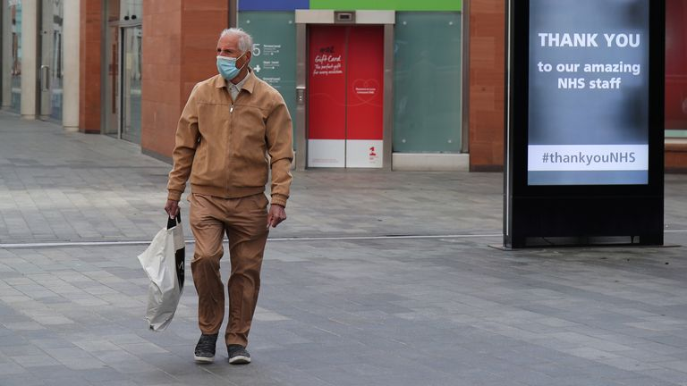 A man wearing a mask is seen among social distancing signs in Liverpool