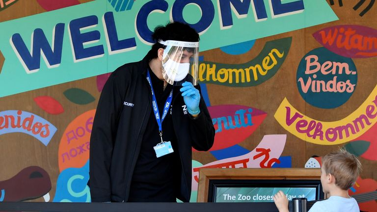 A member of staff welcomes visitors to the London Zoo on the first day of its reopening. Pic: Reuters