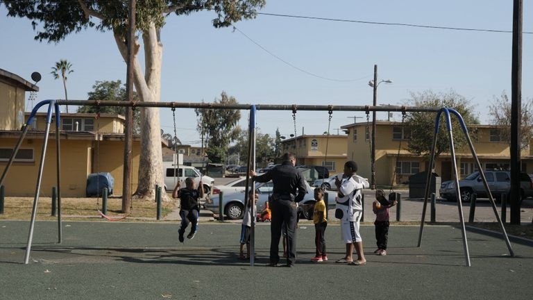 Police talk to some children in Watts, south central LA