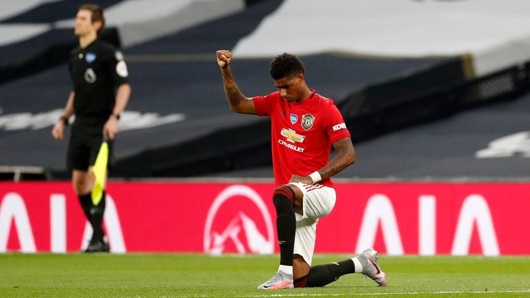 Manchester United's English striker Marcus Rashford (R) takes a knee